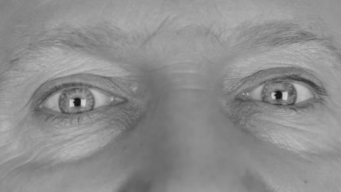 Close-up in black and white on man's eyes, winking one eye and surprised, scare Footage