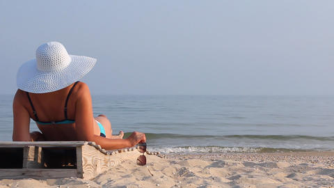 Beautiful slim blonde in a hat on a lounger Archivo