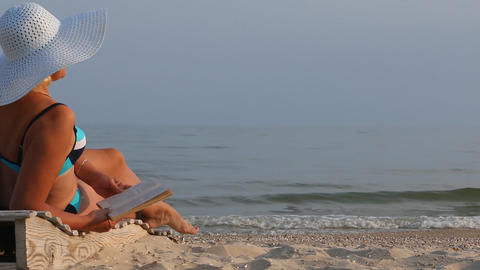 Tanned woman reading a book on the beach Footage