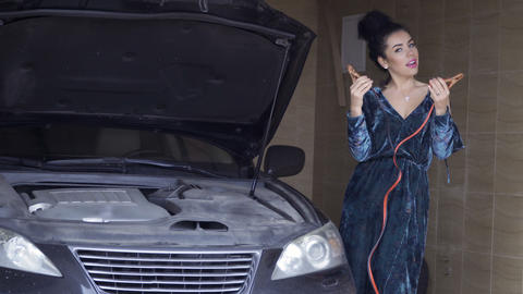 Beautiful brunette wearing long dress with jumper cables Footage