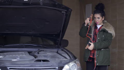 Silly woman fixes the jumper cables on the holder of car hood Footage
