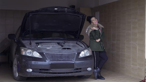 Beautiful woman posing near car in garage with wrench in hand Archivo