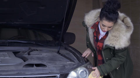 Beautiful woman wipes the car headlamp with a rag Footage
