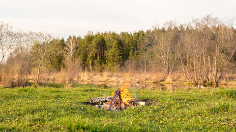 The bonfire flares up and goes out at sunset. Time Lapse Footage