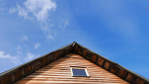 The roof of a wooden house against the background of clouds. Time Lapse Footage