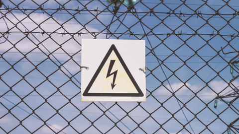 Danger sign of high voltage damage. Electricity of the net. Substation behind Footage