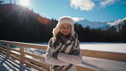 Winter Portrait of a Lady in Fur Hat with Mountains and Sun Flare at Background Footage