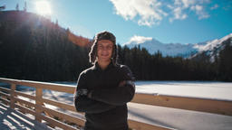 Winter Portrait of a Man in Fur Hat with Mountains and Sun Flare at Background Footage