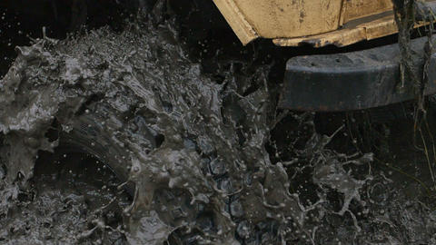 Close-up of a car wheel stuck in the dirty water and mud. Wheel is spinning, but Footage