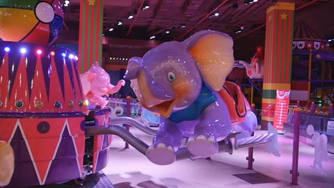 Children attraction. Little girl riding on a child elephant merry-go-round in Footage