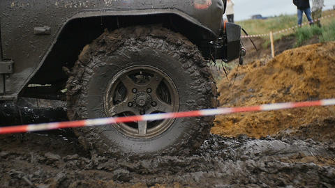close up of wheel in the Mud. Off-road car wheel slips in the mud, but moves Footage