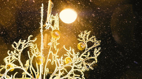 Christmas decoration on the lamppost glows beautifully in the snow, slow motion ビデオ