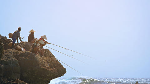 Balinese fishermen angling from the rocks. FullHD footage Footage