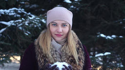 Portrait. A beautiful happy girl blows snow from her hands in the open air in Footage