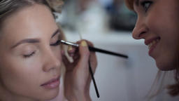 Close-up. Make-up artist does make-up on the clauses of a girl in a beauty salon Footage