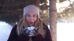 Young happy girl blowing snow from the varek in the open air in sunny winter Footage