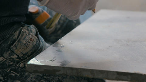 Professional tiling worker measures and marking a tile with pencil. Preparing a Footage