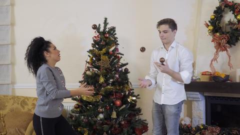 Young guy and girl juggles a Christmas balls Footage