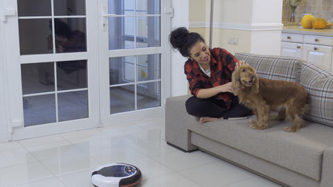 Young woman strokes her dog because he afraid of vacuum-cleaning robot Footage