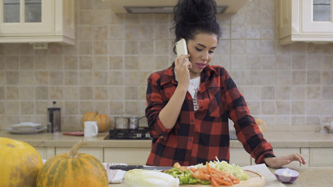 Young womann talks on phone while cooking the dinner at the kitchen Footage