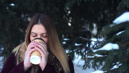 Beautiful young girl drinks coffee in the park in winter Footage