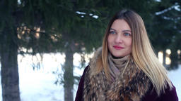 A beautiful fashionable girl walks through a winter park with a good mood and Footage