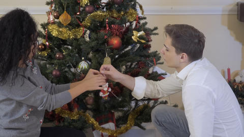 In love couple together hangs a toy on Christmas tree Footage