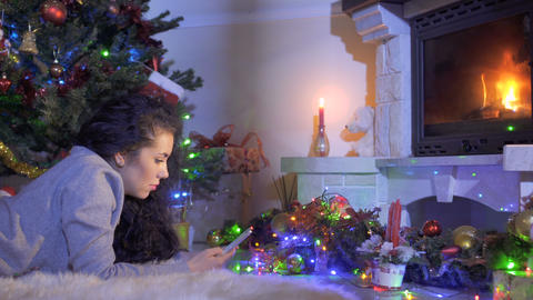 Beautiful woman with phone near Christmas tree and fireplace Footage