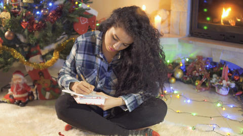 Beautiful sits near Christmas tree and writes a wish list Footage