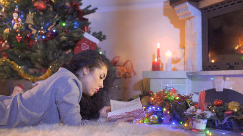 Beautiful brunette read the book near Christmas tree Footage