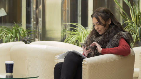 Businesswoman uses phone in the lobby of hotel Footage