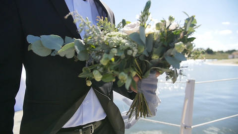 groom holding wedding bouquet in front of the lake in slow motion ビデオ