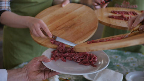 Putting multiple raw meat pieces into the dish Footage