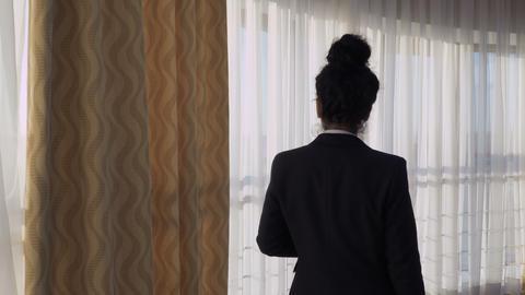 Businesswoman walks near the window in a hotel room Footage