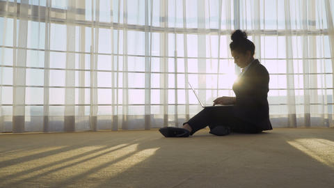 Stylish businesswoman works with laptop near panoramic window Footage