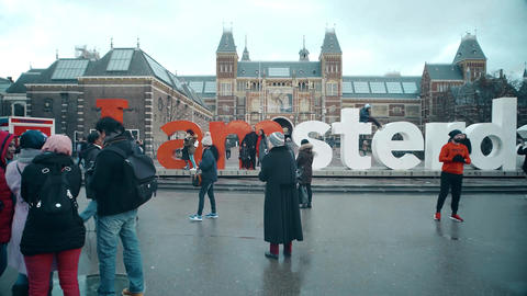 AMSTERDAM, NETHERLANDS - DECEMBER 26, 2017. Tourists taking photos near famous I Footage