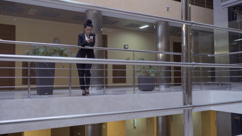 Beautiful brunette in black suit talks on phone in a lobby hall in a hotel Footage