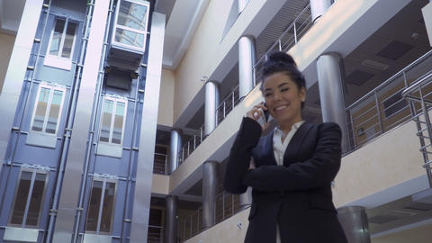 Pretty lady in black suit talks on phone in a hotel Footage