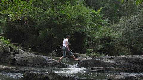 Bare feet Woman walking across mountain river Footage