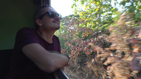 Slow motion video of a man Traveling On The Train Looking Out the open Window Footage