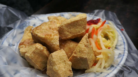 Fried stinky tofu serve on plate with plastic. Famous and iconic fermented tofu  Footage