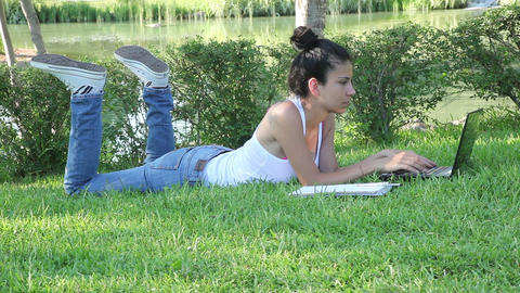 Girl with laptop. Blonde beautiful young woman with notebook sitting on the gras Footage