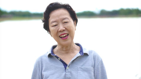 Video of Happy asian senior woman smiling happily in front of nature lake Footage