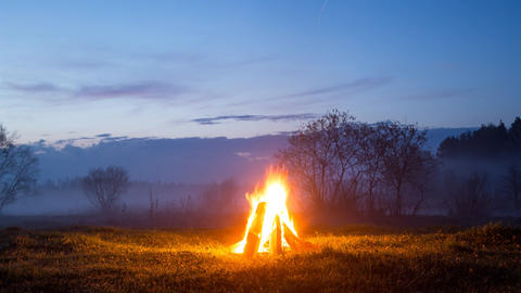 The bonfire flares up and goes out. The night is coming. TimeLapse Footage
