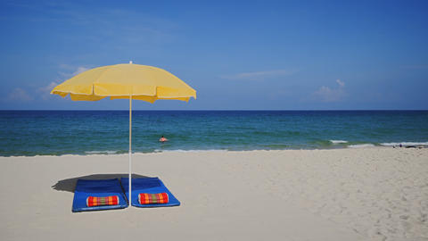 Yellow Umbrella on Tropical Beach Paradise. with Swimming Tourist Footage