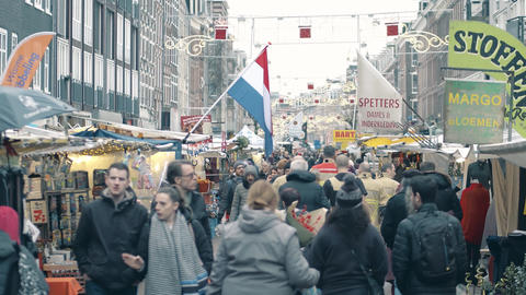 AMSTERDAM, THE NETHERLANDS - DECEMBER 27, 2017. State flag over crowded tourist Footage