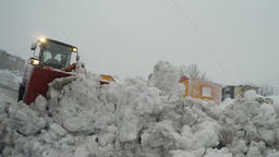 Front end wheel loader clearing wet snow and ice from road, winter road Footage