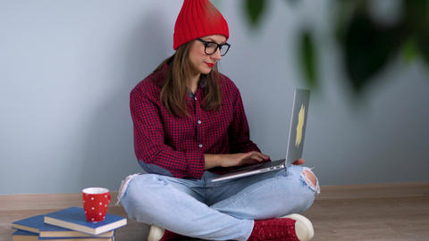 Beautiful girl using laptop and sitting on the floor at home Footage