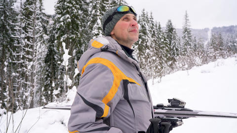 man with skis under his arm rises to the mountain preparing for descent Footage