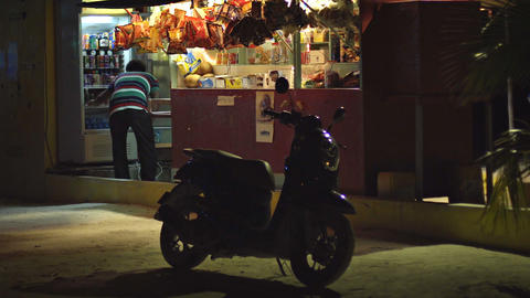 Proprietor of roadside concession stand checks stock of beverages. Maldives Live Action